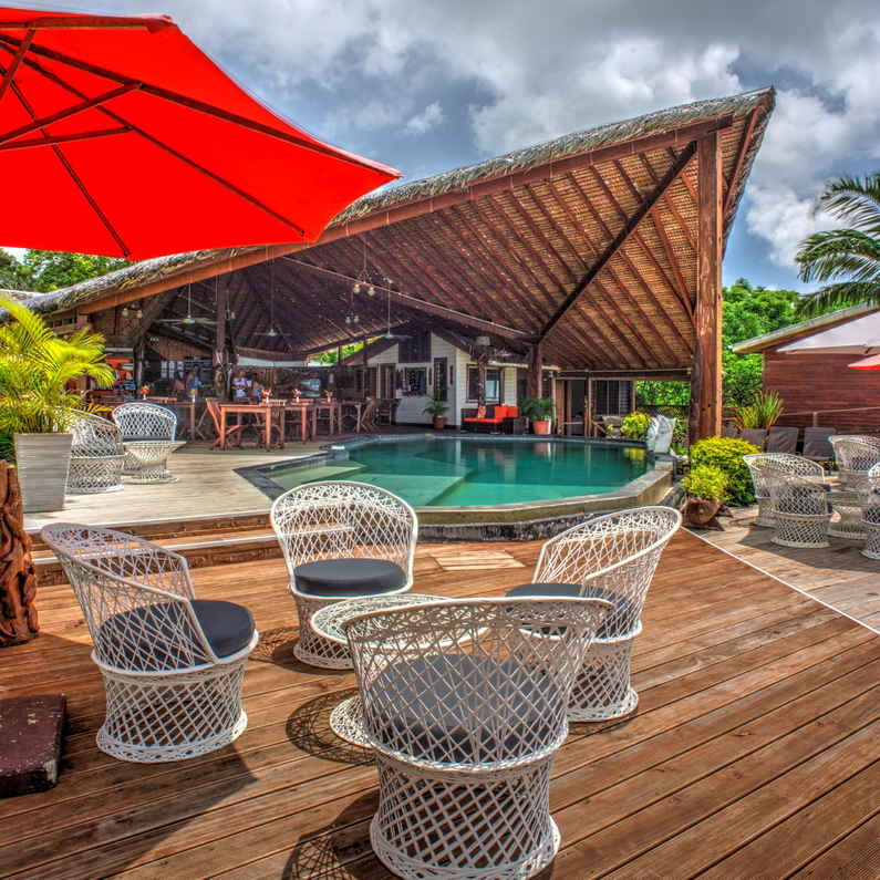 Comfy chairs for relaxing by the pool at Deco Stop Lodge