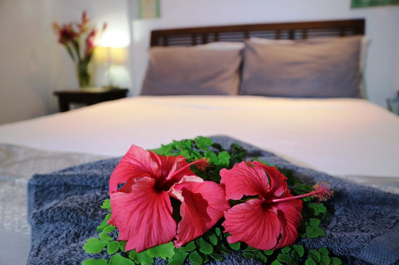 Beautiful Flowers presented on the Main Queen Bed of our Deluxe Family Two Room Unit at Deco Stop Lodge